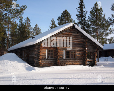 Romantic snow covered log cabin between the trees in a holiday resort in Lapland, Finland. - Stock Photo