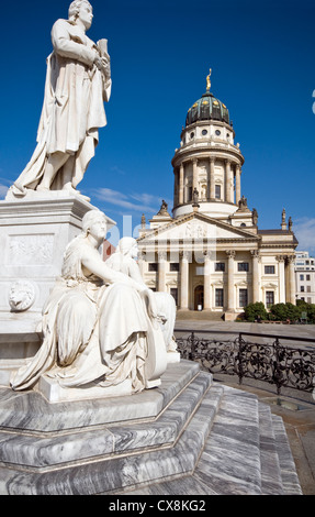 The French Cathedral on the Gendarmenmarkt in Berlin with a marble monument to German poet Friedrich Schiller in - Stock Photo