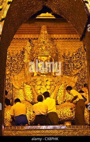 BURMESE MEN gild the much venerated MAHAMUNI BUDDHA inside the MAHAMUNI PAYA built by King Bodwpaya in 1784 - MANDALAY, - Stock Photo