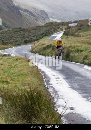 Cyclist on steep hairpin bends on Hardknott pass in English Lake District - Stock Photo