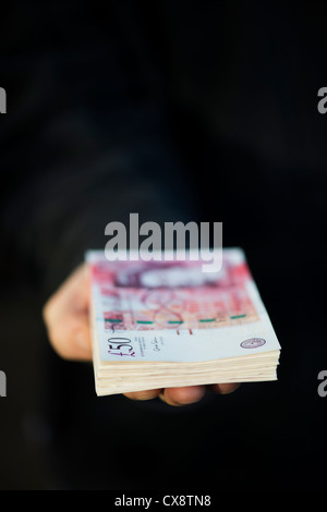 Hand holding Fifty pound notes sterling - Stock Photo