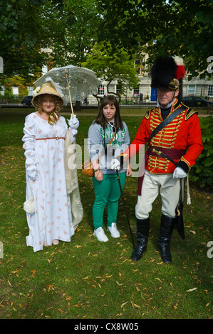 Reenactors in Regency costume pose with tourist in Bath city centre during the 2012 Jane Austen Festival - Stock Photo