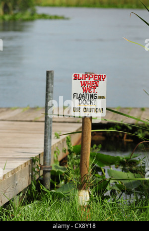 Slippery When Wet sign at dock near pond - Stock Photo