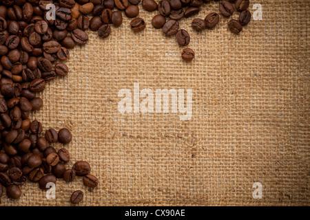 coffee beans on burlap background - Stock Photo