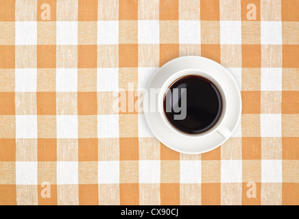 Top view of black coffee cup on brown checked tablecloth - Stock Photo