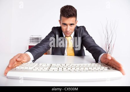 Businessman at his office typing at the computer keyboard - Stock Photo