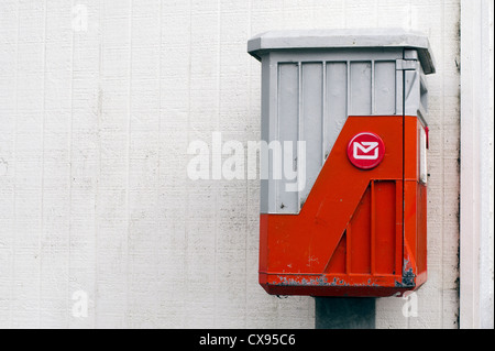 An old mail box against a white wall with space for copy text. - Stock Photo