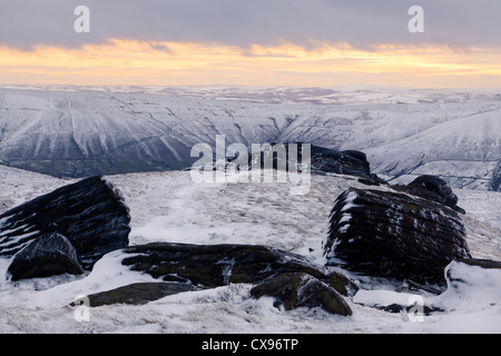 A snow scene at sunset. A Winter landscape view over the Vale of Edale from Kinder Scout, Derbyshire, Peak District - Stock Photo