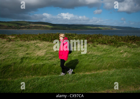 Side View Of A Woman Person Walking Through The Countryside Wearing Waterproof Clothing and A Rucksack - Stock Photo