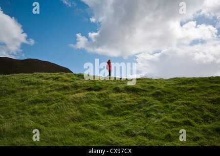 Front View Of A Woman Person Walking Through The Countryside Wearing Waterproof Clothing and A Rucksack - Stock Photo