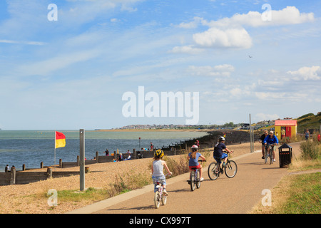 People cycling on Whitstable seafront promenade along Saxon Shore Way in Tankerton Bay to Swalecliffe on north Kent - Stock Photo