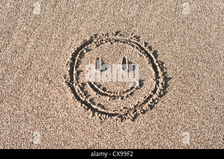 Smiley face drawn on beach sand - Stock Photo