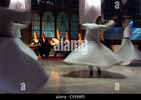 Whirling dervishes and musicians perform tin the event hall of Sirkeci Train Station on October 21, 2005 in Istanbul, - Stock Photo