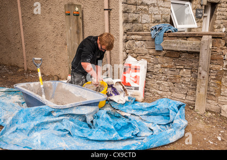 A plasterer mixing plaster in Hawes in Wensleydale , Yorkshire Dales , England , Britain , Uk - Stock Photo