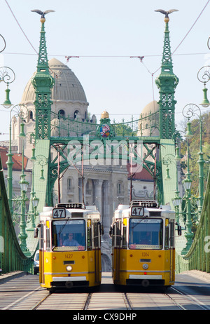 Two trams passing on the Green or Liberty bridge in Budapest, Hungary (Szabadság híd). - Stock Photo