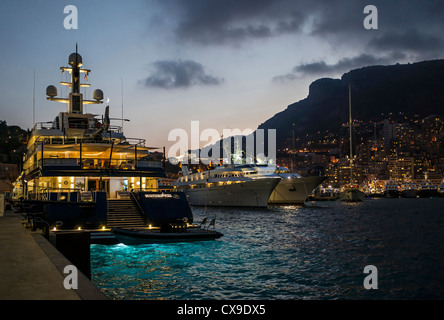 Dusk in Port Hercule, Monaco, with crescent moon above the superyacht on the left. - Stock Photo