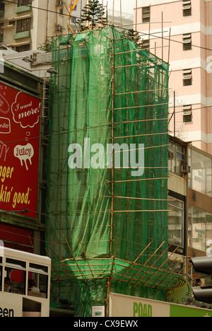 Bamboo scaffolding draped in netting enclose this Hong Kong building. - Stock Photo