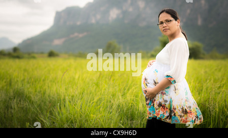 Beautiful Asian woman wearing glasses and affectionately holding her pregnant belly in a newly planted rice field - Stock Photo
