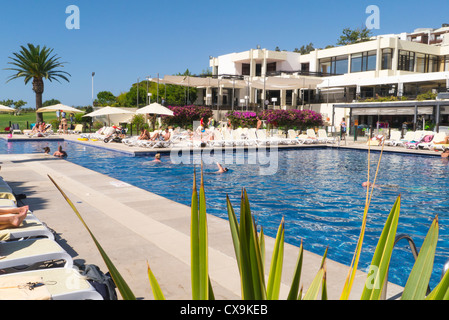 Portugal , Algarve , Club Med , da Balaia , swimming pool surrounded by sun loungers sunbathers & restaurant dining - Stock Photo