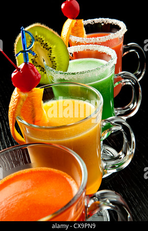 Group of four wine glasses with colored alcoholic cocktails, decorated with fruit and sugar on black bar counter - Stock Photo