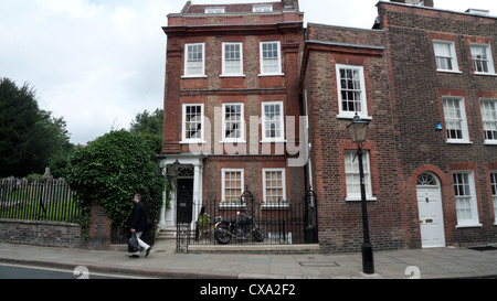 A man walking past Georgian houses in Church Row on the edge of the graveyard in Hampstead Village London NW3 England - Stock Photo