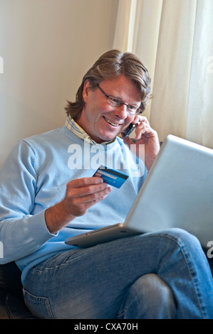 Mature man at home making a financial transaction on line using his laptop computer and an iPhone 4s smartphone - Stock Photo