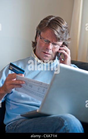 Mature man with credit card at home intently checking paper financial transactions whilst using his laptop computer & speaking on a iPhone smartphone