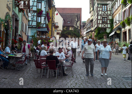 Restaurant street cafe and people in the old town area of Riquewihr Alsace France - Stock Photo