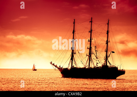 Old tall ship sailing the high seas by the Moon. Flying Dutchman in Blue - Stock Photo