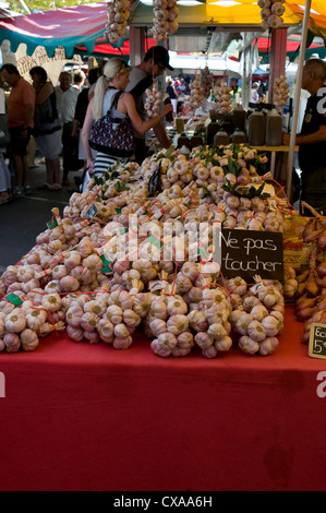 Bunches of Garlic for sale at the Saturday market in Saint-Tropez, France. A sign discourages visitors from touching - Stock Photo