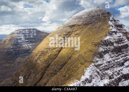 Ben Alligin. The large summit of Sgurr Mhor with snow on the sheltered side with Tom na Gruagaich on the left. - Stock Photo