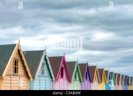 A row of colourful beach huts under a stormy sky - Stock Photo