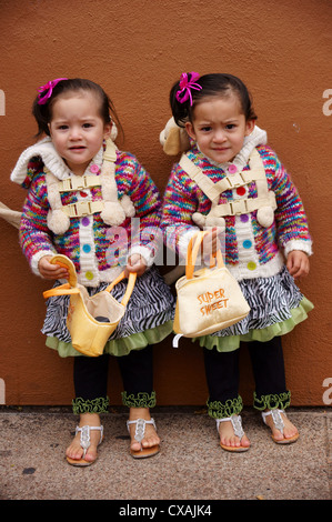portrait headshot of twin baby hispanic latino girls toddlers females in stern look wonder fear surprise cute - Stock Photo