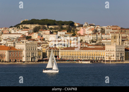 View from River Tagus, showing Praca Comercio, with demonstration, castle and cathedral, Lisbon, Portugal, Europe - Stock Photo