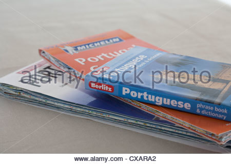 two maps of Portugal and a Berlitz Portuguese Phrase book and dictionary - Stock Photo