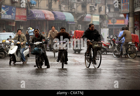 Shanghai, cyclists on a wet road - Stock Photo