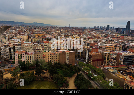 Aerial panoramic view of the crowded tall buildings city of Barcelona contrasted with open green park below from - Stock Photo