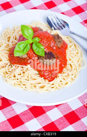 Meatballs and spaghetti with marinara sauce on a white plate - Stock Photo
