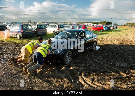 Volunteers pushing a car stuck in the mud at the Eisteddfod Genedlaethol Cymru 2012 / National Eisteddfod of Wales - Stock Photo