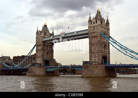 Tower Bridge in Central London with the river Thames in the foreground on a cloudy overcast day - Stock Photo