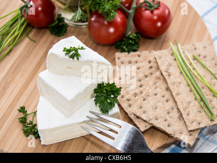 Camembert with Crispbread and Herbs on a cutting board - Stock Photo
