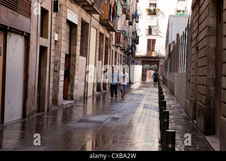 Two young men walk down this freshly washed street, finally turning into one of the apartment buildings in Barcelona, Spain.