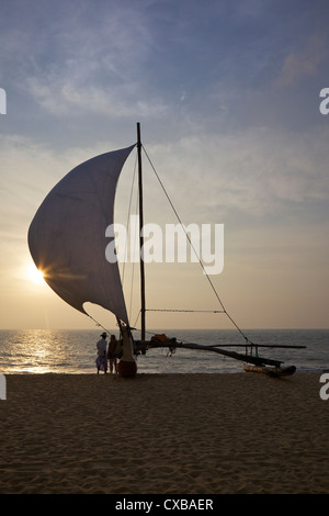 Fisherman and Oruvas (traditional outrigger dug-out canoe), on Negombo beach, Sri Lanka, Asia - Stock Photo