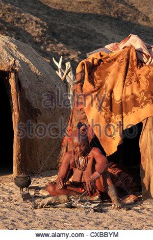 Himba woman sitting outside her hut, Purros village, northern Kaokoland, Namibia, Africa - Stock Photo