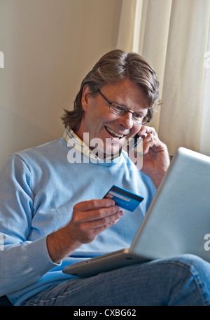 Mature man at home happily making a financial transaction on line using his laptop computer and an iPhone 4s smartphone - Stock Photo