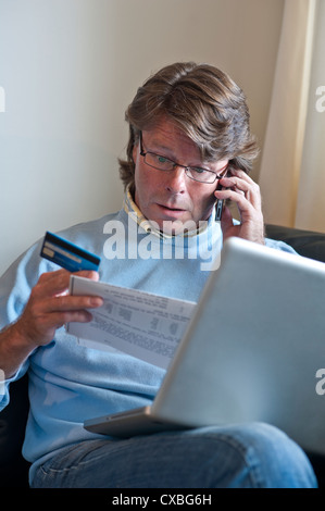 CREDIT BANK CARD STATEMENTS Worried mature man at home with a laptop computer on the telephone checking fraud credit bank card financial transactions
