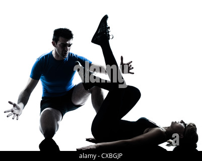 caucasian aerobics instructor  with mature woman exercising fitness workout in silhouette studio isolated on white - Stock Photo