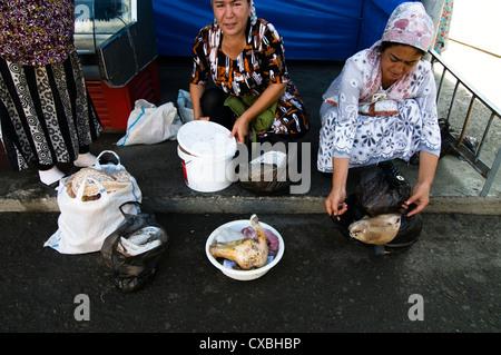 Local Uzbek women sell meat in Tashkent's Chorsu bazaar. - Stock Photo