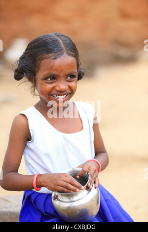 Indian school girl with water pot rinsing her mouth and washing her face Andhra Pradesh South India - Stock Photo