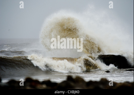 Waves crash over rocks in an area known as South Gare on Teesside in England as heavy seas lash the coastline. - Stock Photo